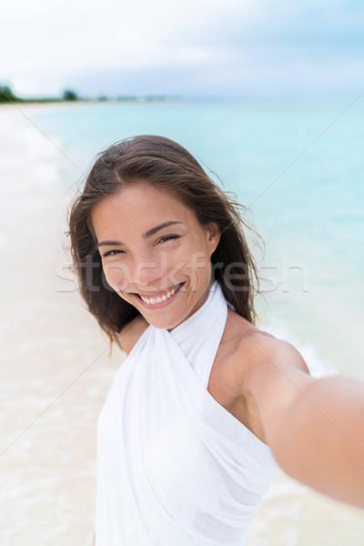 Selfie of beautiful Asian mixed race woman on beach wearing white cover-up Stock photo © Maridav