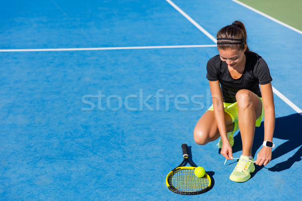 Tennis player woman tying shoe laces on court Stock photo © Maridav