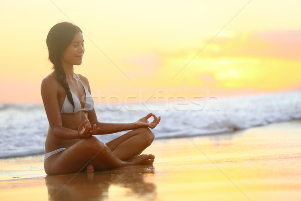 Relaxante ioga mulher meditando praia pôr do sol Foto stock © Maridav