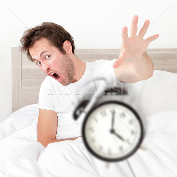 Man waking up late for work early throwing alarm Stock photo © Maridav