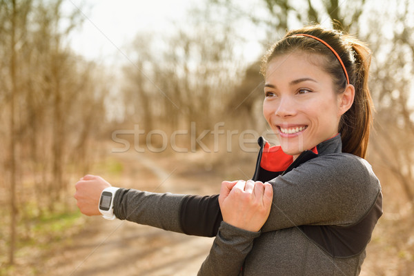 Fitness woman stretching arms with smartwatch Stock photo © Maridav