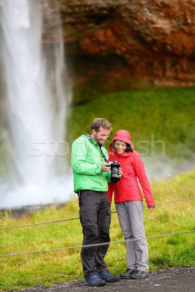 Tourists with SLR camera by waterfall on Iceland Stock photo © Maridav