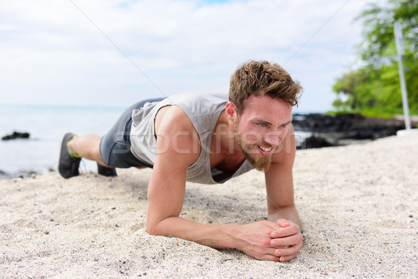 Man training core fitness doing plank on beach Stock photo © Maridav