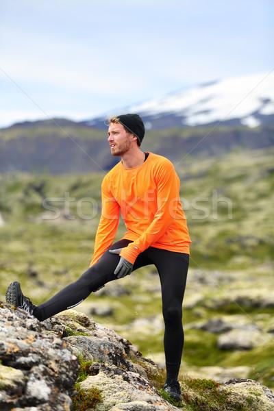 Runner man stretching legs after running trail run Stock photo © Maridav