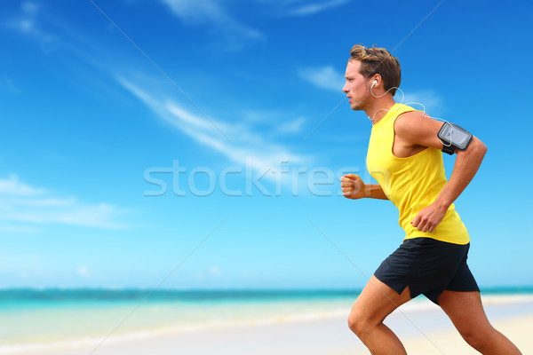 Runner running listening smartphone music on beach Stock photo © Maridav