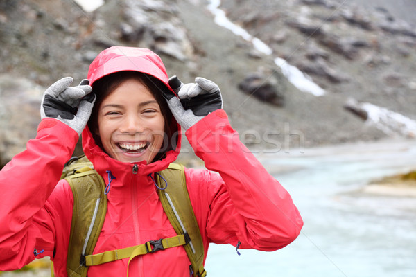 Laughing happy woman hiking with backpack in rain Stock photo © Maridav