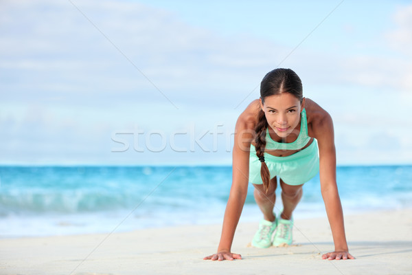 Fitness beach woman smiling planking doing yoga plank pose core exercises Stock photo © Maridav