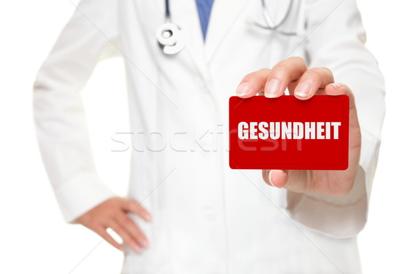 Doctor holding GESUNDHEIT card in german Stock photo © Maridav