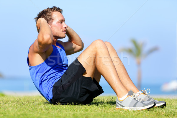 Sit-ups - fitness man training sit up outside Stock photo © Maridav