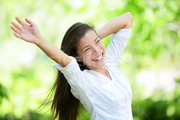 Joyful Young Woman Raising Arms In Park Stock photo © Maridav