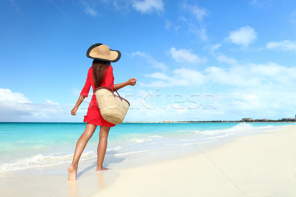 Beachwear woman walking with sun hat and beach bag Stock photo © Maridav
