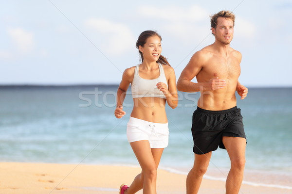 Couple running - sport runners jogging on beach Stock photo © Maridav