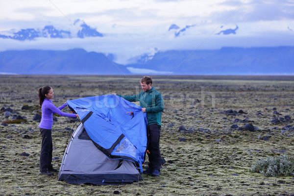 Stock photo: Tent - people pitching tent on Iceland at dusk