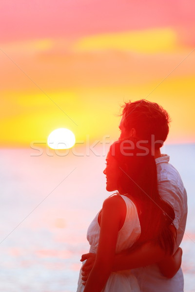 Happy couple watching sunset at beach vacation Stock photo © Maridav