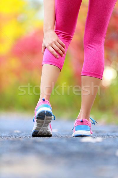 Stock photo: Woman running clutching calf muscle injury