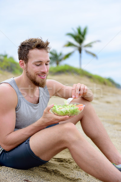 Healthy fit man eating organic vegan food on beach Stock photo © Maridav