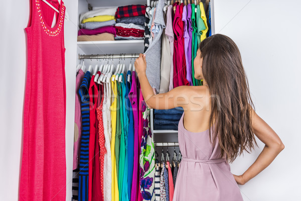 Woman choosing clothes to wear in clothing closet Stock photo © Maridav