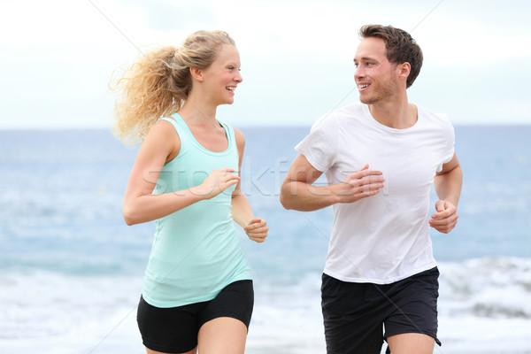 Running couple jogging exercising on beach talking Stock photo © Maridav