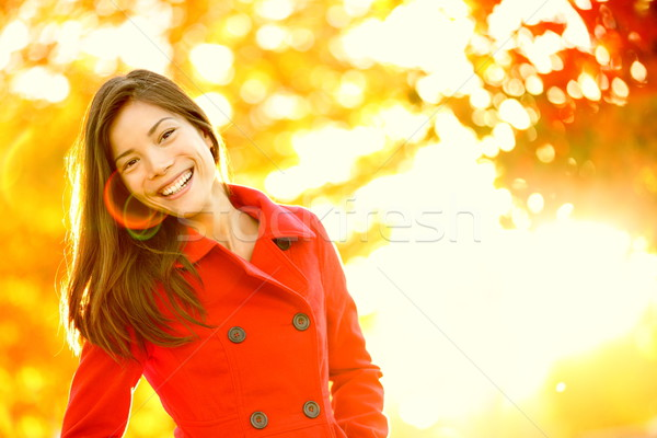 Autumn red trench coat woman in sun flare foliage Stock photo © Maridav