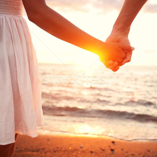 Amor romântico casal de mãos dadas praia pôr do sol Foto stock © Maridav