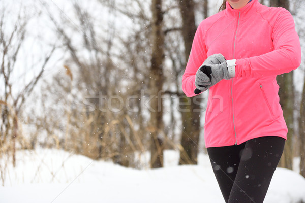 Runner using smartwatch jogging running in winter Stock photo © Maridav