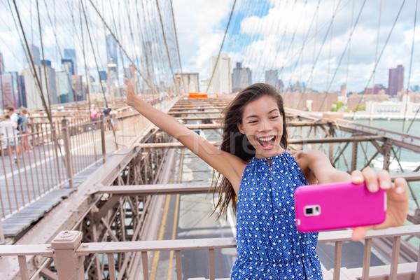 Happy selfie tourist woman taking fun phone picture on Brooklyn Brige, New York Stock photo © Maridav
