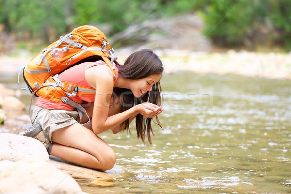 Hiker woman drinking water from river creek hiking Stock photo © Maridav