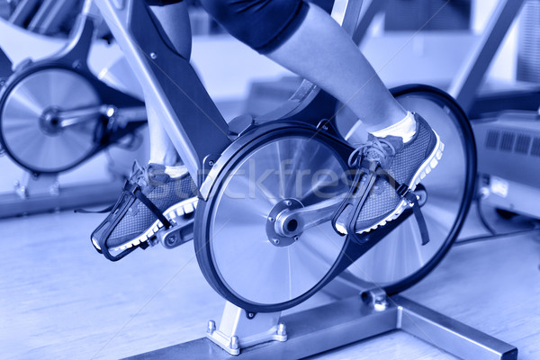 Exercise bike with spinning wheels - woman biking Stock photo © Maridav