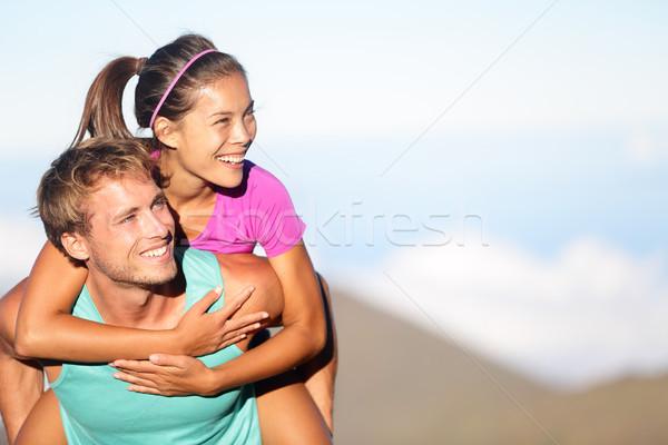 Happy young couple piggybacking outside Stock photo © Maridav