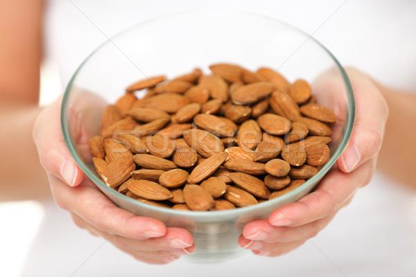 Almonds - woman showing raw almond bowl close up Stock photo © Maridav