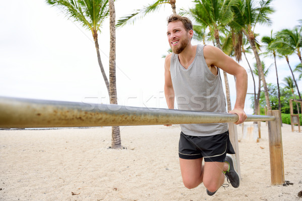 Bodyweight exercises man workout on dips bars Stock photo © Maridav