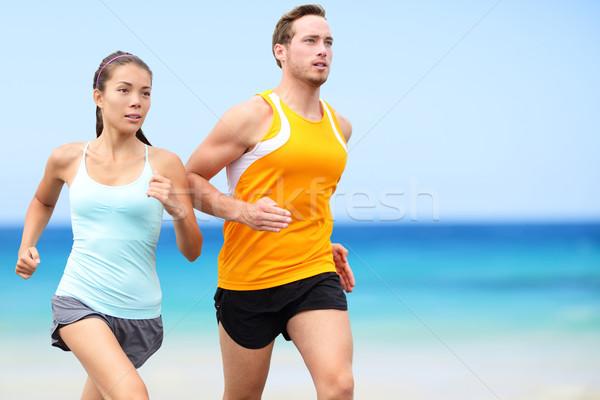 Runners running on beach - jogging couple Stock photo © Maridav