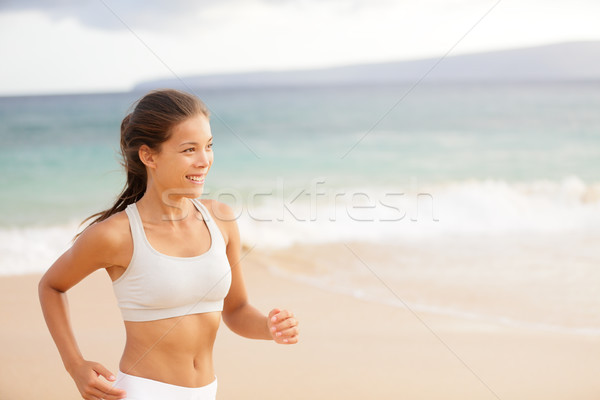 Athletic young woman running on the beach Stock photo © Maridav