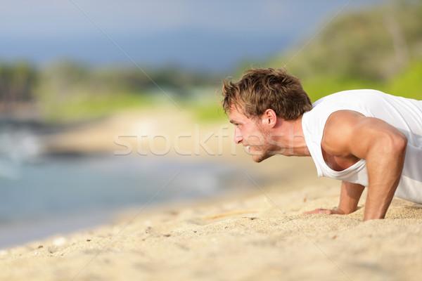 Sit-ups - man fitness model training on beach Stock photo © Maridav