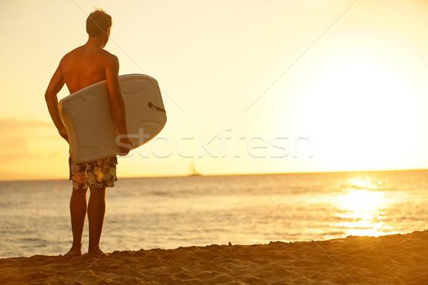 Szörfös férfi tengerpart naplemente tart fitt Stock fotó © Maridav