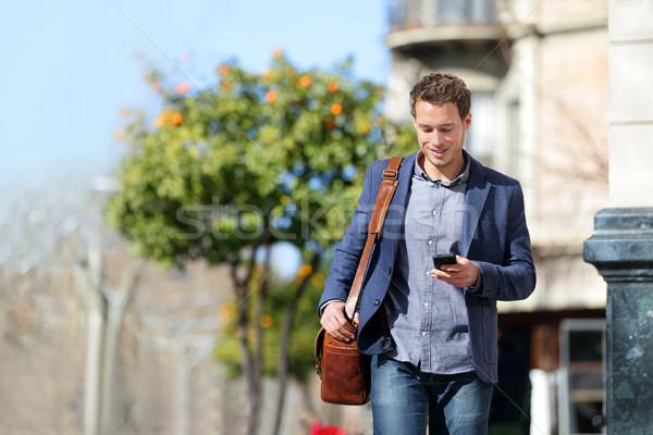 Business man using mobile phone walking to work Stock photo © Maridav