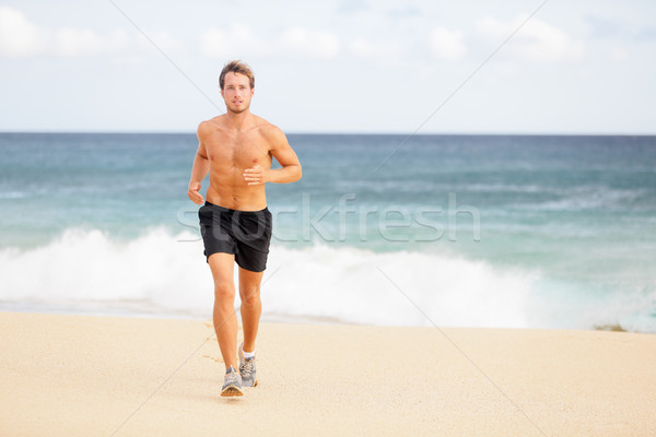 Runner - Young man jogging on the beach Stock photo © Maridav