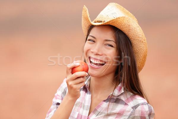 American cowgirl eating peach smiling happy Stock photo © Maridav