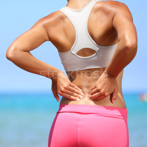 Back pain - woman having injury in lower back Stock photo © Maridav