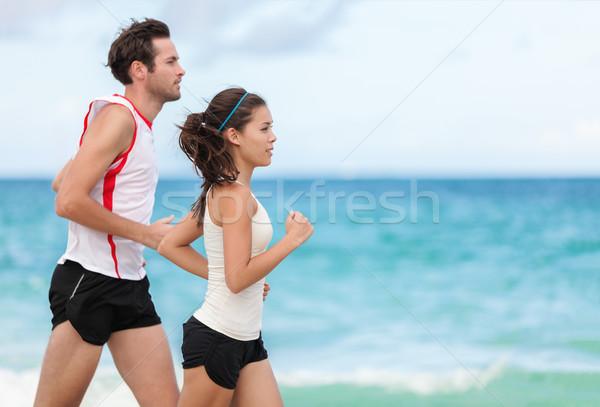 Fitness interracial couple runner running on beach Stock photo © Maridav
