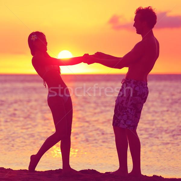 Stock photo: Lovers couple having fun romance on sunset beach