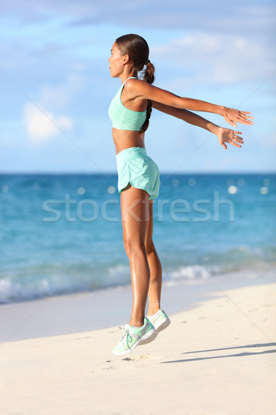 Fit woman training legs with hiit workout jumping squats exercises on beach Stock photo © Maridav