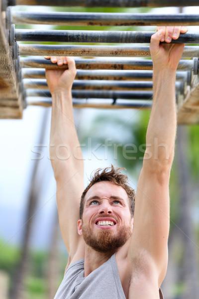 Fit man cross training outside on monkey bars Stock photo © Maridav