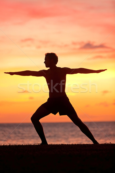 Yoga man training and meditating in warrior pose Stock photo © Maridav