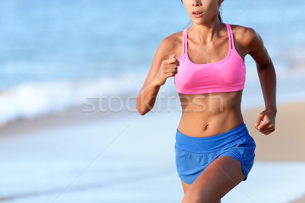Midsection Of Determined Woman Jogging On Beach Stock photo © Maridav
