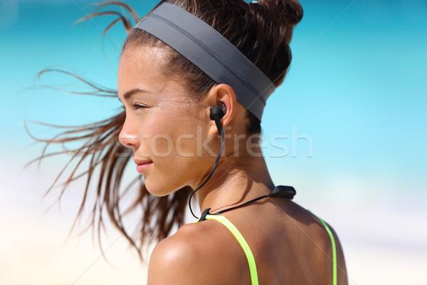 Fitness girl with sport in-ear wireless headphones Stock photo © Maridav
