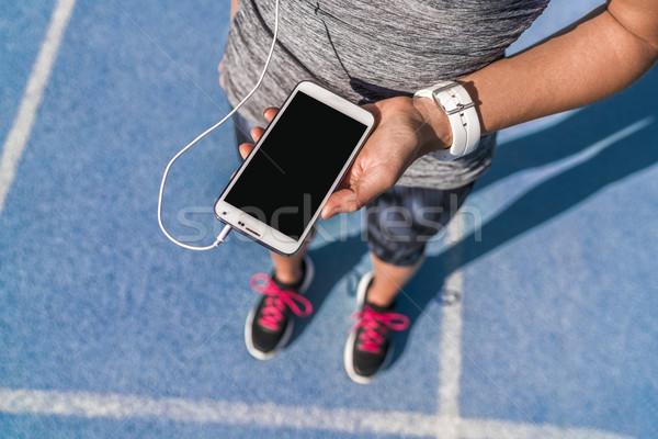 Runner girl phone screen music for running track Stock photo © Maridav