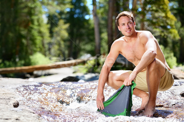 Camping hiker man on trek washing clothes in river Stock photo © Maridav