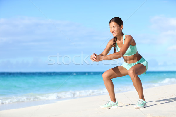 Fitness young Asian woman training legs with squat exercise on beach Stock photo © Maridav