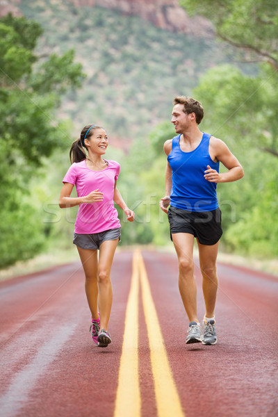 Two people jogging for fitness running on road Stock photo © Maridav